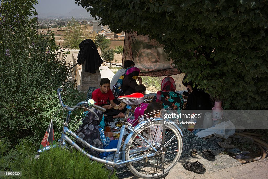 A family participates in a picnic outside the Shah Agha shrine September 4, 2015 during traditional Friday prayer services in Kabul, Afghanistan.