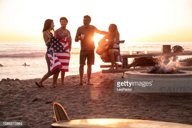 family party on the beach in california at sunset - independence day stock pictures, royalty-free photos & images