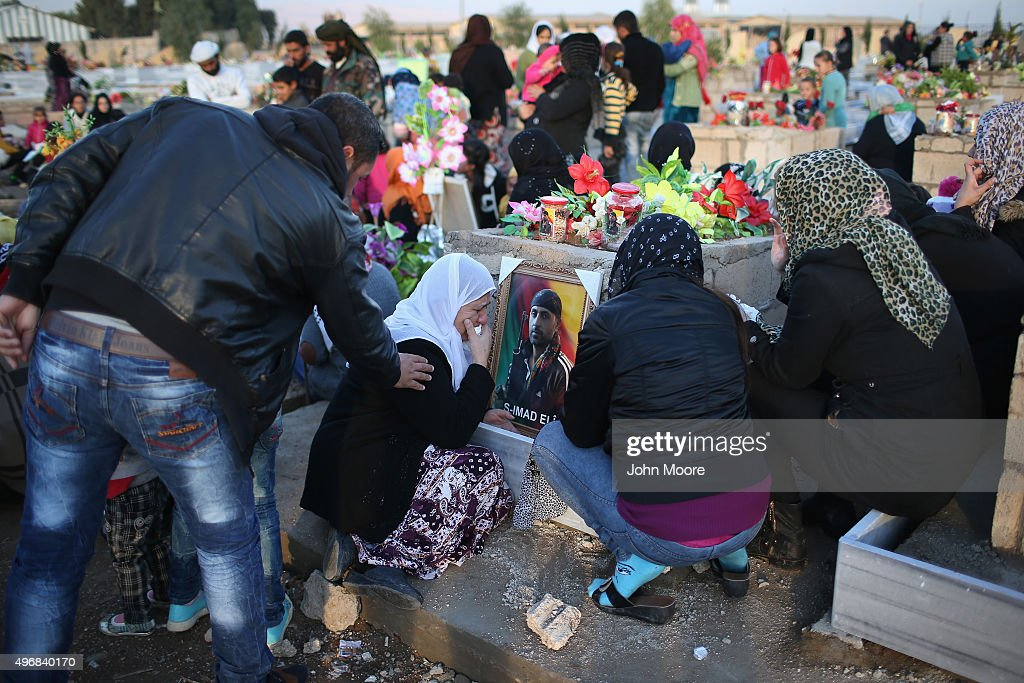 A family pays respects a grave in a martyrs' cemetery for soldiers from the People's Protection Units (YPG), killed fighting ISIL on November 12, 2015 in Qamishli, Rojava, Syria. The predominantly Kurdish regions of northern Syria and Iraq have become bastions against the Islamic State, with the help of U.S. airstrikes. In Iraq, Kurdish Peshmerga forces launched an offensive to drive the extremists from Sinjar, which they had captured in 2014, killing and enslaving thousands of minority Yazidis.