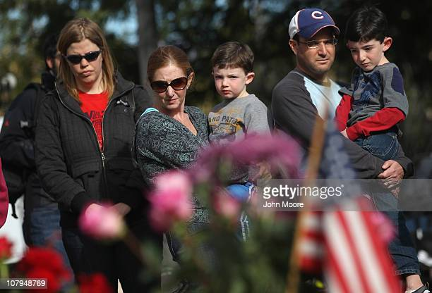 A family pays their respects at a makeshift memorial outside the University Medical Center for those killed or wounded during the attack on US Rep...