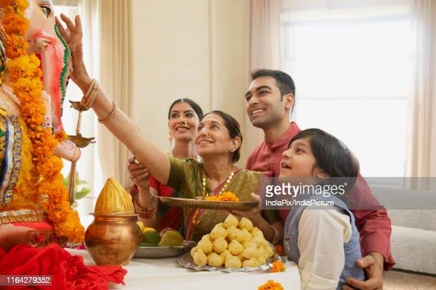 family perfoming ganpati aarti on ganesh chaturthi at home - hinduism stock pictures, royalty-free photos & images