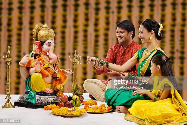 family performing a pooja - ganesh chaturthi stock photos and pictures