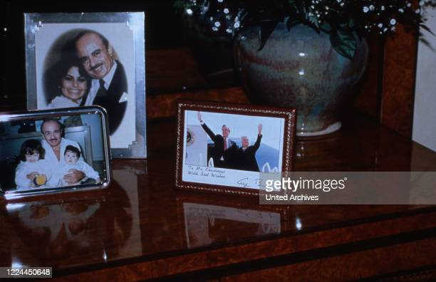 Family photographs from Adnan Khashoggi at his desk in his office at Olympic Tower in New York USA 1986