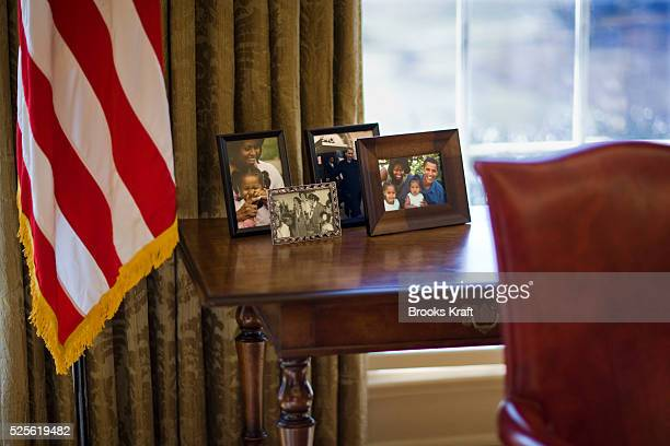 Family photos of President Barack Obama behind his desk in the Oval Office at the White House in Washington