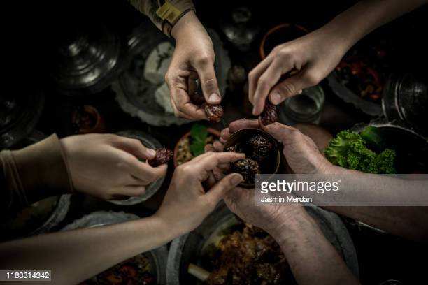 family picking dates before dinner - ramadan stock pictures, royalty-free photos & images