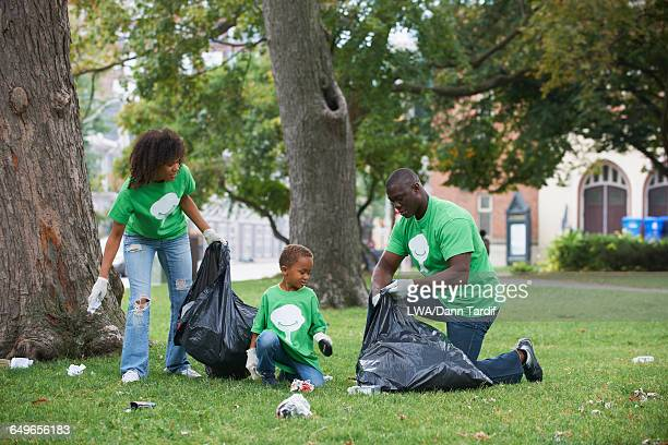 family picking up garbage in park - city cleaning stock pictures, royalty-free photos & images