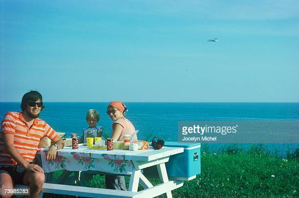 Family picnic on a ledge by the sea