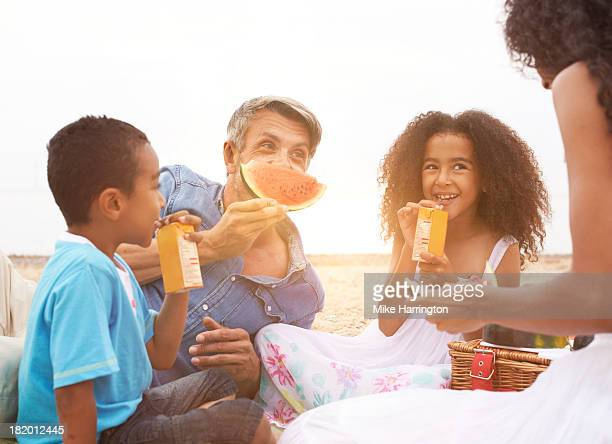 family picnic on beach. father playing with food. - picnic stock pictures, royalty-free photos & images