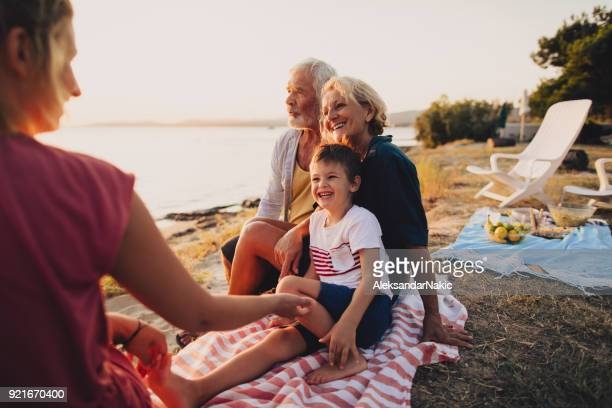 family picnic on the beach - candid beach stock photos and pictures