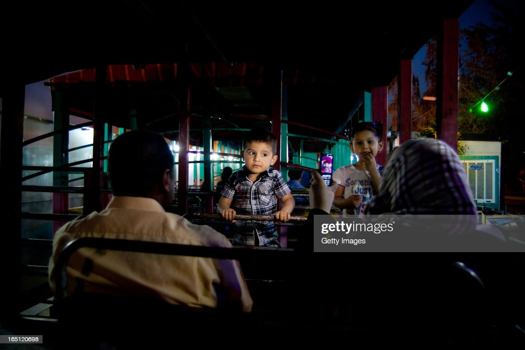 A family pictured on a ride in Zawra Park on March 28, 2013 in Baghdad, Iraq. Ten years after the regime of Saddam Hussein was toppled from power, Baghdad continues to show the scars of the war. In vast areas, infrastructure is fractured and basic services are lacking, however, some areas of the capital are showing promising signs of recovery.