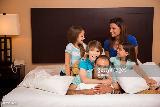 Family piles on dad in hotel bedroom.  Vacation. Happy, laughing.