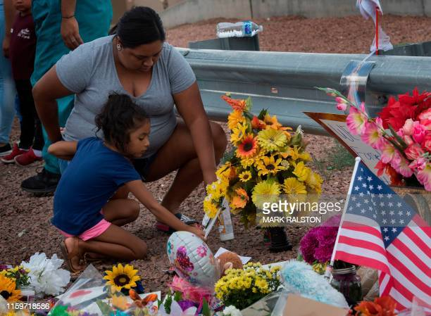 A family places flowers at a makeshift memorial outside the Cielo Vista Mall WalMart where a shooting left 20 people dead in El Paso Texas on August...