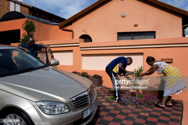 Family plants a tree outside their upmarket house on February 1, 2014 in Diepkloof section, Soweto, South Africa. Soweto is a mix of old housing and...