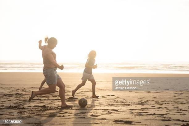 a family play football on the beach at sunset - new zealand stock pictures, royalty-free photos & images