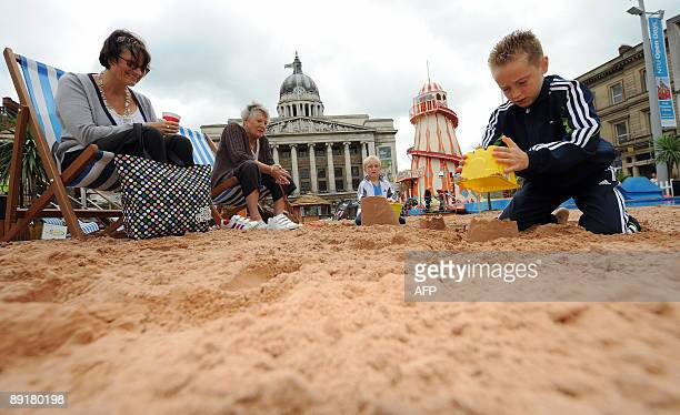 Family play on a beach at the launch of the 'Nottingham Riviera', Britain's largest urban beach in Nottingham, central England, on July 22, 2009....