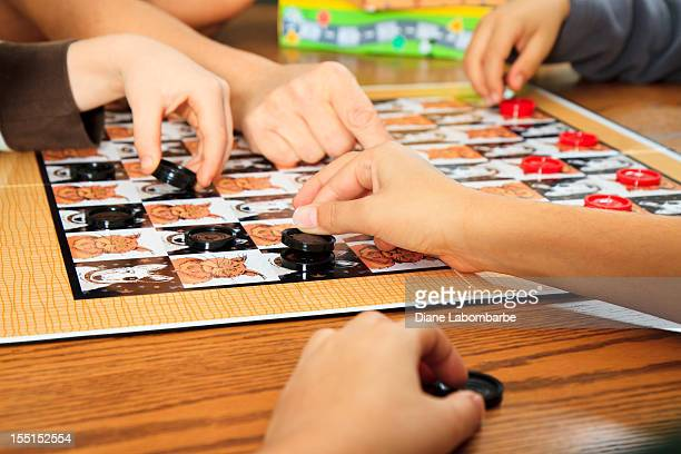 family playing a board game together - game night stock photos and pictures