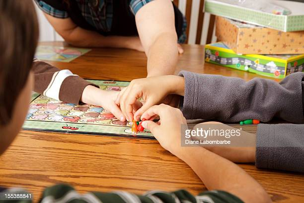 family playing a board game together - game board stock photos and pictures