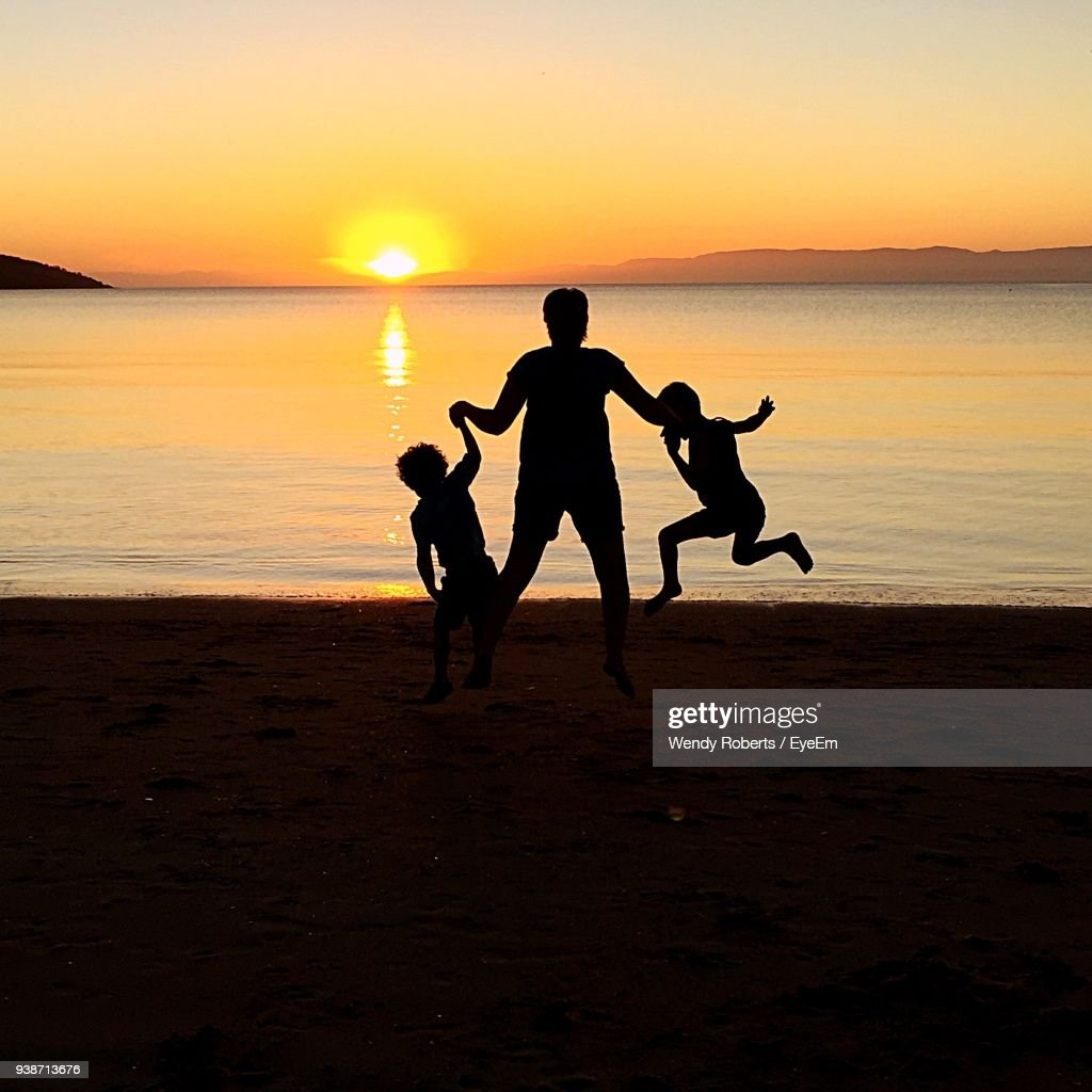 Family Playing At Beach Against Sky During Sunset : Stock Photo