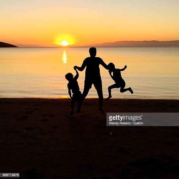 Family Playing At Beach Against Sky During Sunset