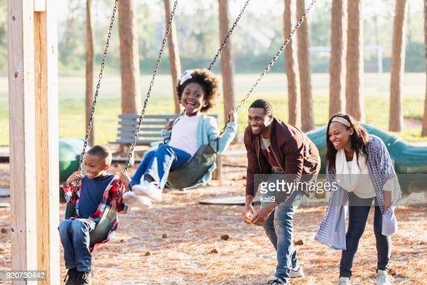 family playing at park together, on swings - minority groups stock pictures, royalty-free photos & images
