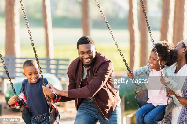 Family playing at park together, on swings