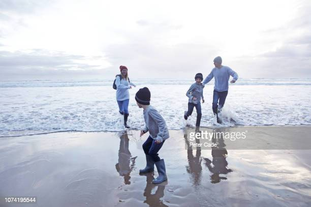 family playing at waters edge on beach in winter - two generation family stock pictures, royalty-free photos & images