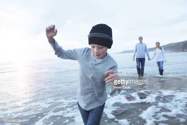 family playing at waters edge on beach in winter - loslassen aktivitäten und sport stock-fotos und bilder