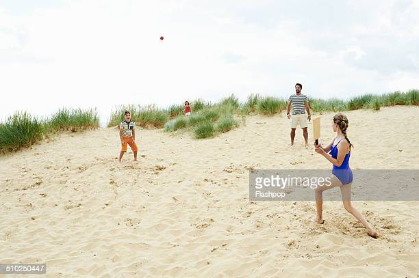 Family playing ball game at the beach