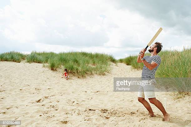 family playing ball game at the beach - beach cricket stock pictures, royalty-free photos & images