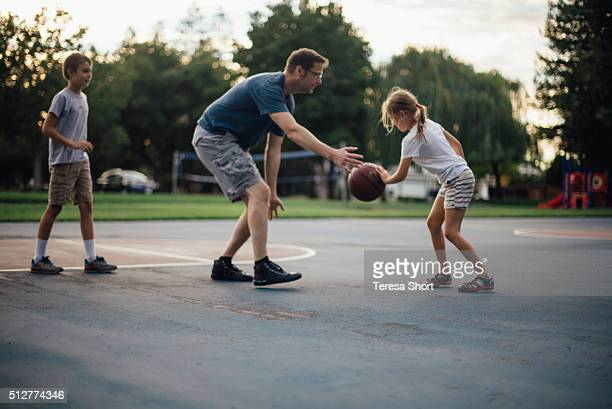 Family playing basketball togethe outdoors
