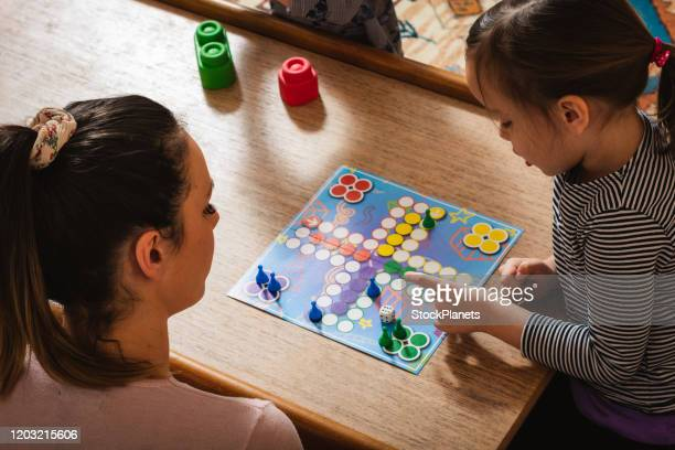 family playing board game at home. - leisure games stock pictures, royalty-free photos & images