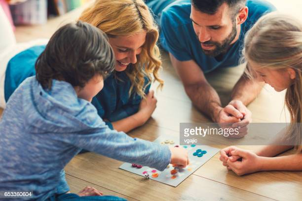 family playing board game at home - leisure games stock pictures, royalty-free photos & images