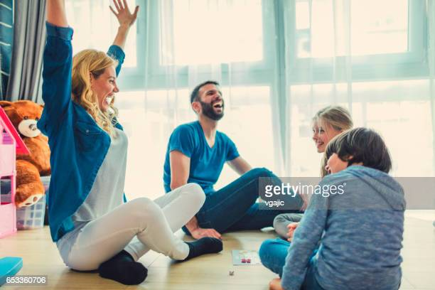 family playing board game at home - board game stock pictures, royalty-free photos & images