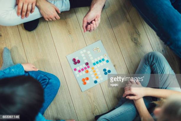 family playing board game at home - game board stock photos and pictures