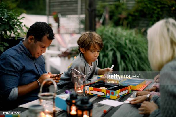 family playing board game on table while father using mobile phone - board game stock pictures, royalty-free photos & images