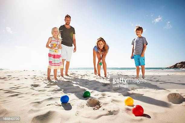 Family playing boules on beach