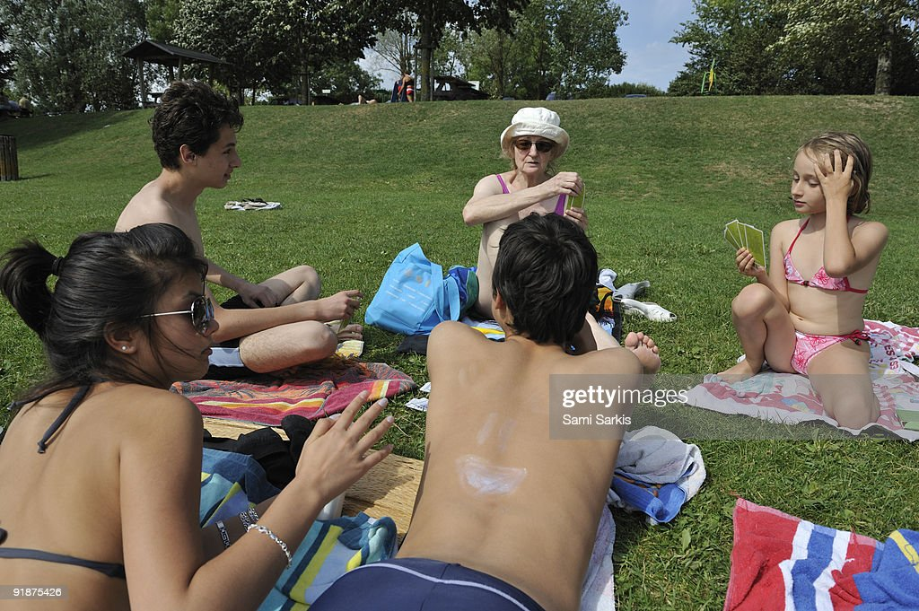Family playing cards at beach, lying on grass : Stock Photo