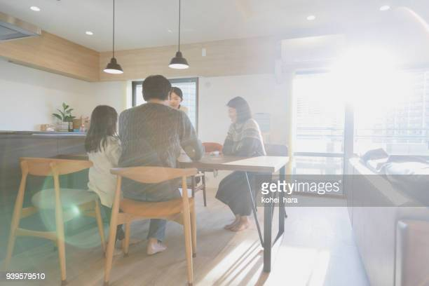 family playing cards at home - comfortable stock pictures, royalty-free photos & images