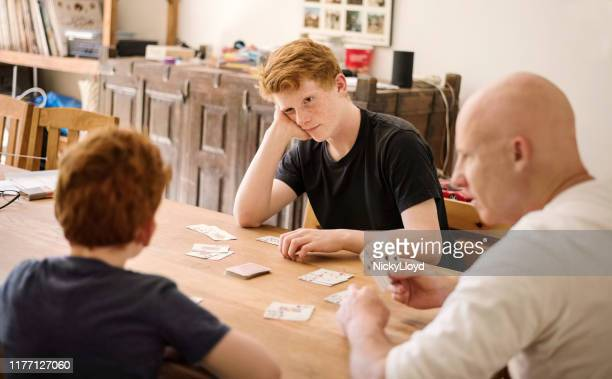 family playing cards together - hand of cards stock photos and pictures