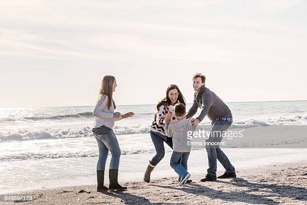 Family playing catch on the she shore in winter