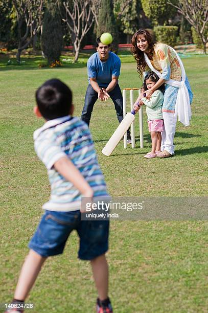 Family playing cricket in a lawn, Gurgaon, Haryana, India