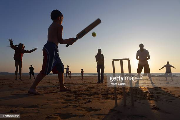 family playing cricket on beach at sunset - beach cricket stock pictures, royalty-free photos & images