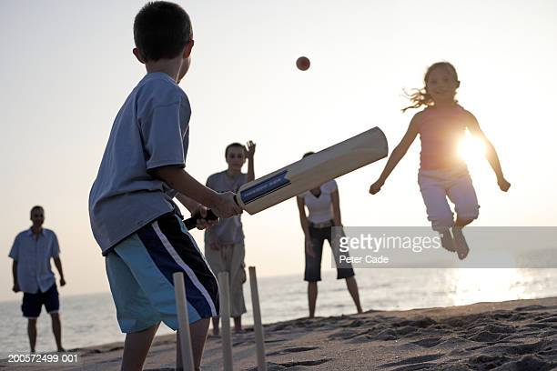 family playing cricket on beach - beach cricket stock pictures, royalty-free photos & images