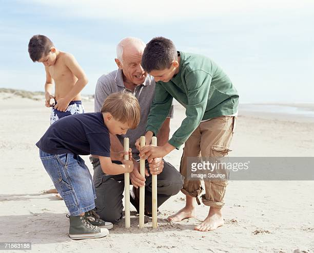family playing cricket - beach cricket stock pictures, royalty-free photos & images