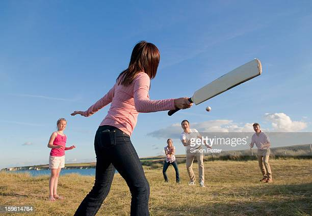 Family playing cricket together outdoors