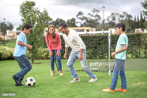Family playing football at the park