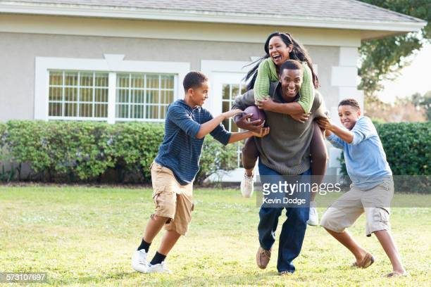 family playing football in backyard - african american family home stock photos and pictures