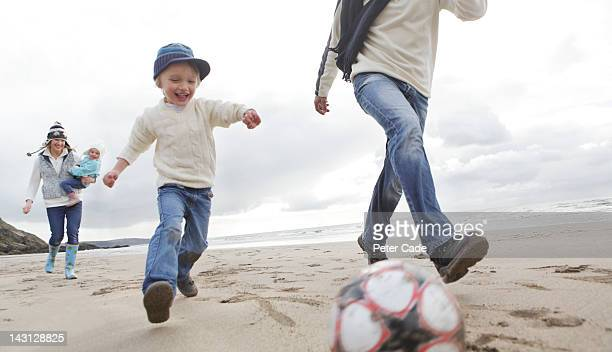 family playing football on beach in winter
