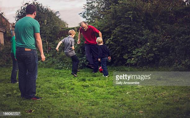 family playing football together in the garden - grandfather stock pictures, royalty-free photos & images