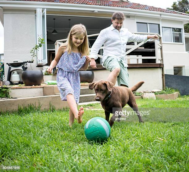 Family playing football with the dog